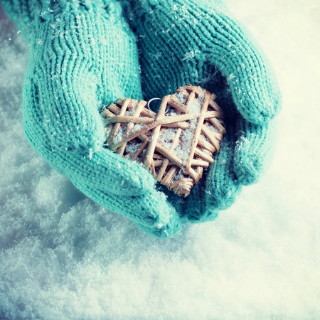 Female hands in teal knitted mittens with a entwined vintage romantic heart on a snow background. Love and St. Valentine concept.