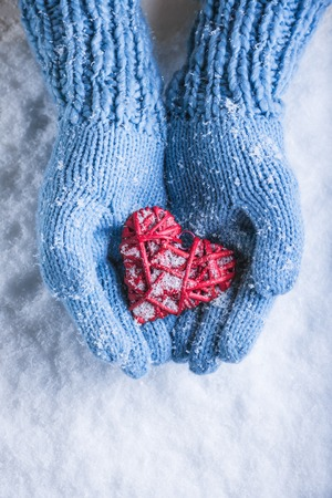 entwined: Female hands in teal knitted mittens with a entwined vintage romantic heart on a snow background. Love and St. Valentine concept.