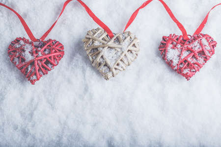 Three beautiful romantic vintage hearts are hanging on a red band on a white snow winter background. Love and St. Valentines Day concept. Фото со стока