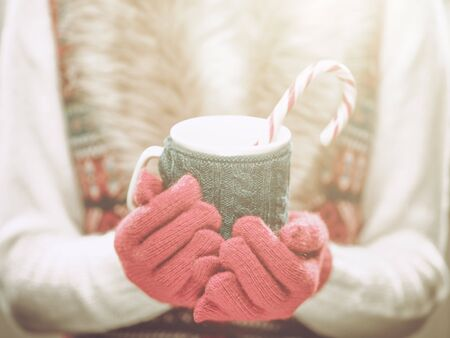 Woman holding winter cup close up on light background. Woman hands in woolen red gloves holding a cozy mug with hot cocoa, tea or coffee and a candy cane. Winter and Christmas time concept. Фото со стока