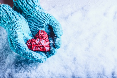 Woman hands in light teal knitted mittens are holding a beautiful a entwined vintage romantic red heart in a snow background. Love and St. Valentine concept. Standard-Bild