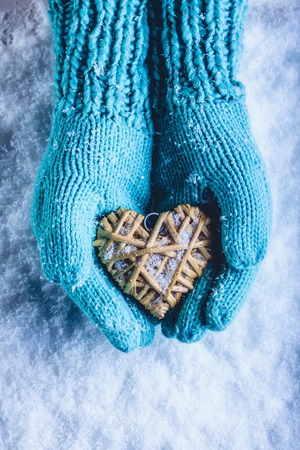 Female hands in light teal knitted mittens with entwined beige flaxen heart on a white snow winter background. Love and St. Valentines Day cozy concept. Фото со стока