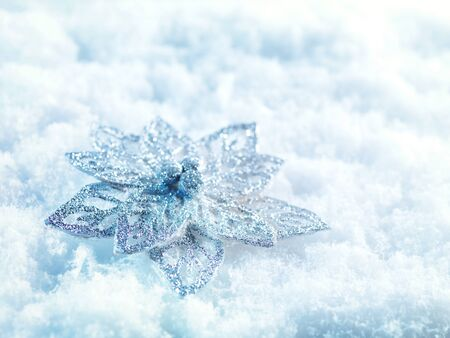 Winter and Christmas background. Beautiful sparkling silver and red Christmas decoration on a white snow background. Ornamental Christmas concept. Close up with copy space.