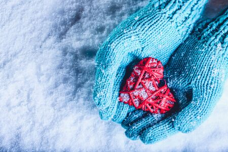Woman hands in light teal knitted mittens are holding a beautiful a entwined vintage romantic red heart in a snow background. Love and St. Valentine concept. Stock Photo