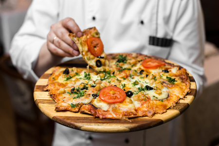White Wood Fired Neapolitan Pizza Maker Close Up Holding Silver Tray with Fresh Pie Stock Photo