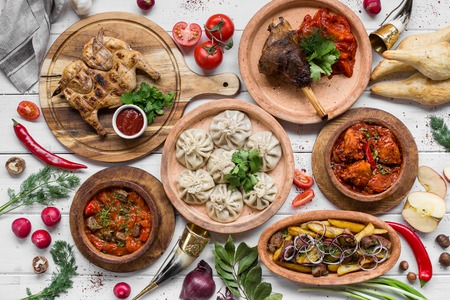 A lot of food on the wooden table. Georgian cuisine. Top view. Flat lay . Khinkali and Georgian dishes Stock Photo