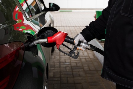 refilling: Close-up photo of hand holding fuel pump and refilling car at petrol station Stock Photo