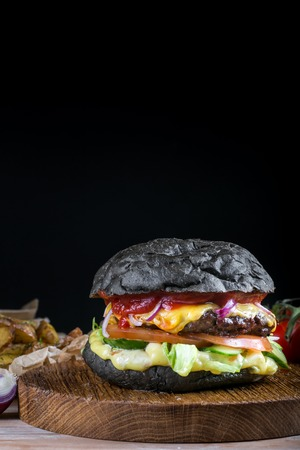 Fresh tasty burger on black background. Homemade hamburger with beef, onion, tomato, lettuce and cheese with ingredients