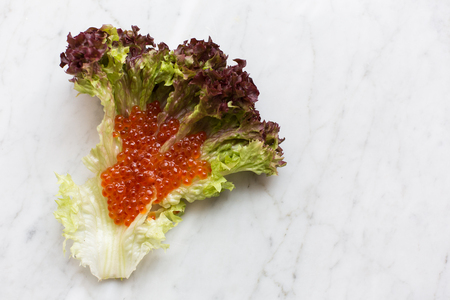 Top view of red caviar on a salad leaf on a light marble background. copy space, Top view