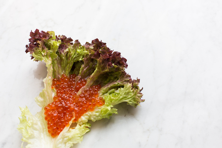Top view of red caviar on a salad leaf on a light marble background. copy space, Top view. close up