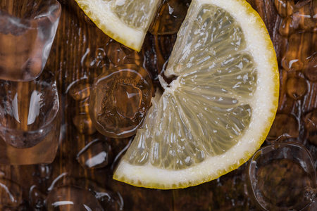 cocktail mixer: ice cube and sliced lemon on wooden table, top view. close up. Stock Photo