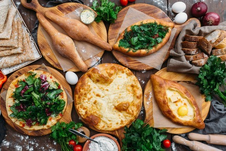 Traditional Georgian adjara khachapuri and Kolkh khachapuri on the table. Homemade baking. Top view. Flat lay