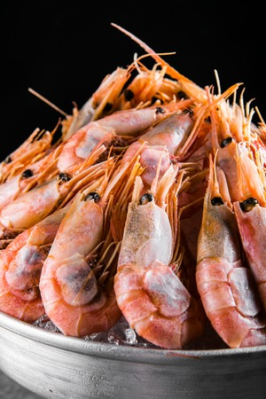 cooked Shrimps in a metal bucket on a dark background