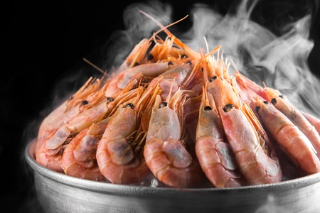 Cooked shrimps in a misted metal bucket on a dark smoky background