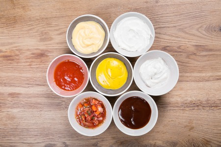 Set of sauces - ketchup, mayonnaise, mustard soy sauce, bbq sauce, mustard grains and pomegranate sauce on wooden table Stock Photo