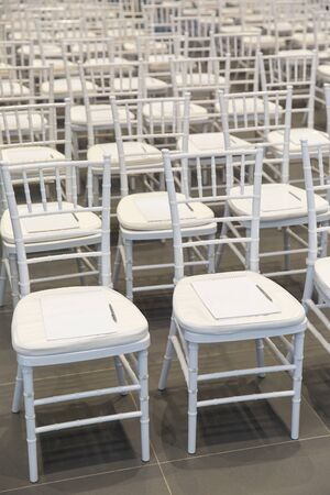 A row of white chairs in the audience is white. Pen and notebook for writing on chairs