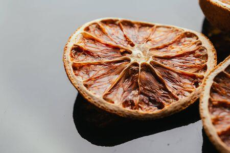 christmas scent: dry lemon and orange on a dark mirror background. Stock Photo