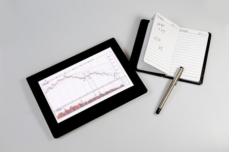 a tablet computer with Stock K-line on the screen and a notebook with a pen