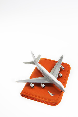 a plane lay on a passport holder with a white background