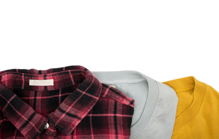 Top view folded T shirts and plaid shirt isolated on white background Stock Photo
