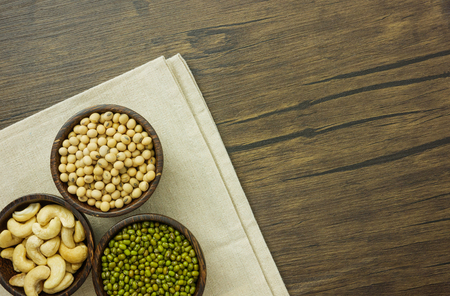 Flat lay assorted beans including cashews soybeans and green beans on wooden table with copy space