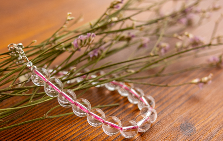 Crystal quartz bracelet on wooden table and flowers