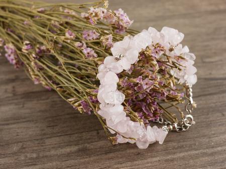 Close up rose quartz bracelet and flower bouquet on wooden table