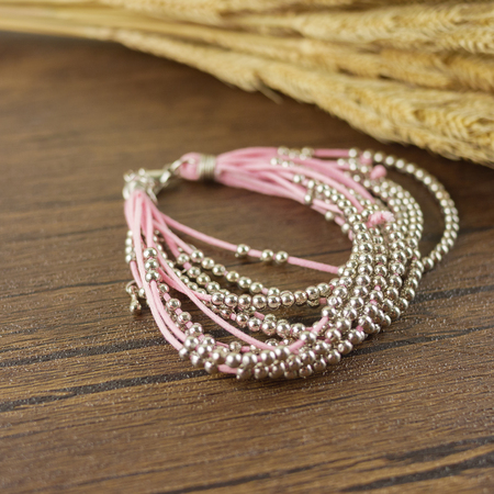 Pink multi strand bracelet on wooden background with dry grass Stock Photo