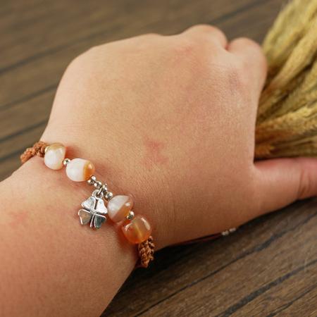 Women wrist wear brown beaded bracelet on wooden background