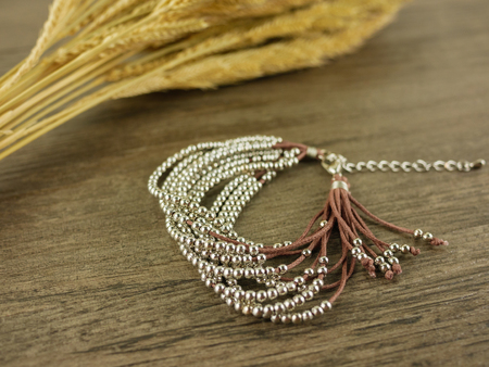 Brown multi strand bracelet on wooden background with dry grass