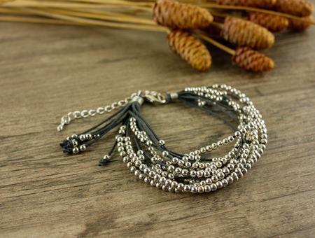 Black multi strand bracelet on wooden background with dry grass