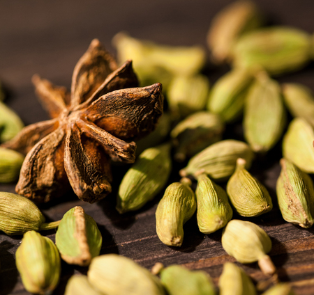 Cardamom and stars anise on wooden background