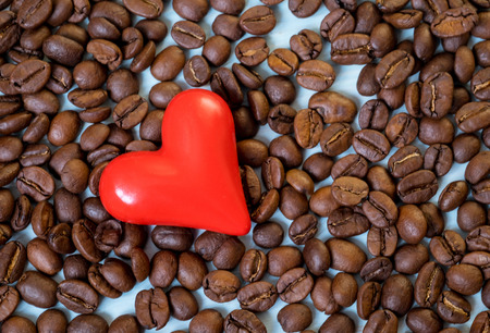 Ceramic red heart and coffee beans - beautiful background