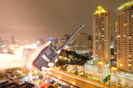 Hand holding radio on city landscape at background