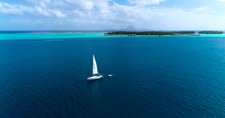 sailboat in aerial view with bungalow in background, French Polynesia