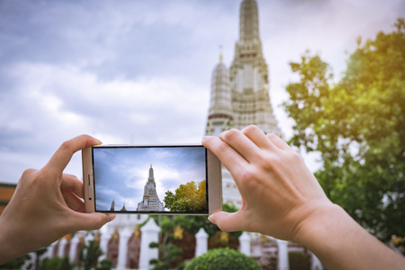 women hand taking photos With a smartphone at the Wat Arun temple on vacation Bangkok Thailand. Stock Photo