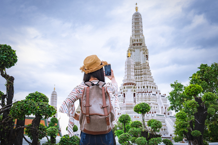 Asian woman tourists are taking photos With a smartphone at the Wat Arun temple on vacation Bangkok Thailand. Stock Photo