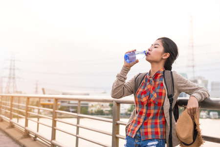 Asian girl Drinking water Stay tired of thirst tourist backpack relax time on holiday.
