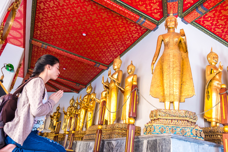 Asian women tourist backpack is worshiping the image of Buddha in holiday at wat pho Bangkok Thailand. It is a landmark and attraction. Stock Photo
