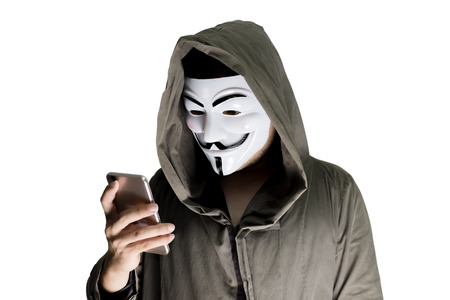 Bangkok, Thailand - May 6, 2018 : A hacker wears a mask wearing a robe. using smartphone theft and attacking data on cyberspace. Isolated on white background