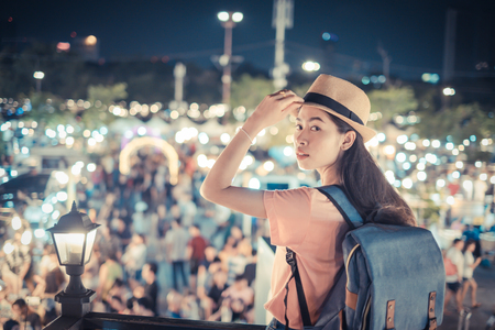 Portrait asian woman tourist backpacker and hat stand watch the night market with so many people for shopping fashion product in holiday and relax Imagens