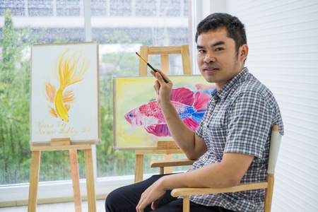 Young man asian or artist figure is sitting the drawing. using ideas to think and elaborate on the beautiful fish. and create the best artwork. Reklamní fotografie