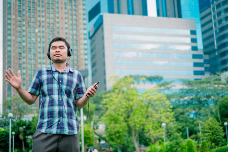 Asian young man listening to music from a smartphone using headphones. At public park the city center happy and relax On his vacation. she is 25-30 years old. Stock Photo