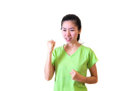 Asian women wear green shirts expressed his joyful victory and fighting using fists. smiling happily. isolated on white background and clipping path.