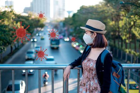 During the epidemic crisis colona 2019. asian woman tourists to travel on his holidays. She wears a mask to protect the virus from Covid-19 and Dust pm 2.5