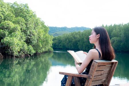 Asian women sitting reading. River view with mangrove forest. And the clear skies with beautiful clouds. Suitable for tourism, recreation and relax and intend To study knowledge