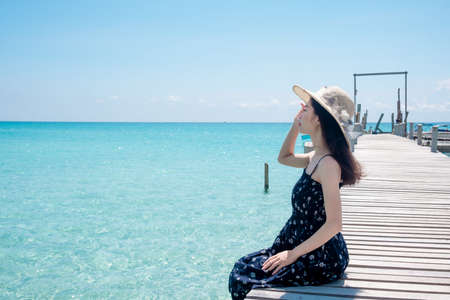 Asian woman tourists Sitting on a wooden bridge at the beautiful sea view. the clear skies with clouds. Is a tourist destination that is perfect for relaxing on holidays. 免版税图像