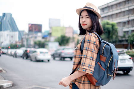 Asian female tourist Standing pose, street photography While traveling in the capital On a happy holiday. 免版税图像