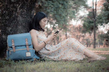 Asian woman tourist A smartphone under the tree. To read social news online. At the public park. It is a relaxing place in vacation lifestyle.