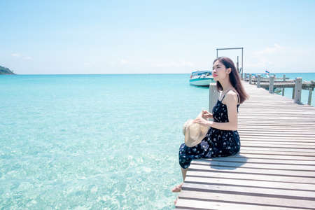 Asian woman tourists Sitting on a wooden bridge at the beautiful sea view. the clear skies with clouds. Is a tourist destination that is perfect for relaxing on holidays. 版權商用圖片